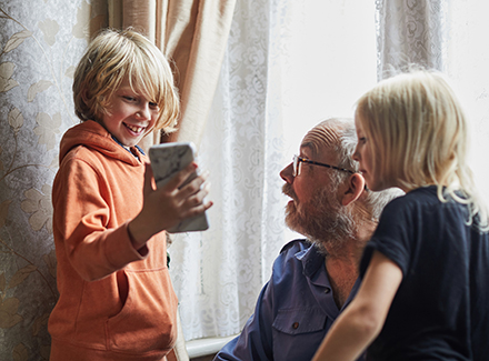 Granfather talking with children holding a mobile