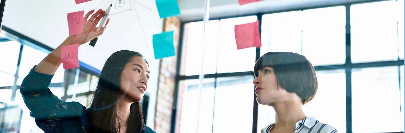 To kvinner foran glassvegg med Post-it-lapper